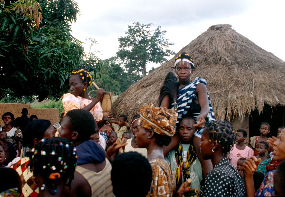 """Jeunes filles portées sur les épaules de leur oncle pour la cérémonie du """"klin"""" (culte dirigé par les femmes âgées, qui gèrent l'excision des petites et jeunes filles). Golipla. Photo Daniela Bognolo, 1999."""