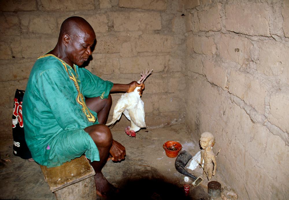 Le devin-guérisseur mona Lorou Zigbé accomplit les sacrifices et les libations préalables à la divination. Bambalouma. Photo Alain-Michel Boyer, 1999.