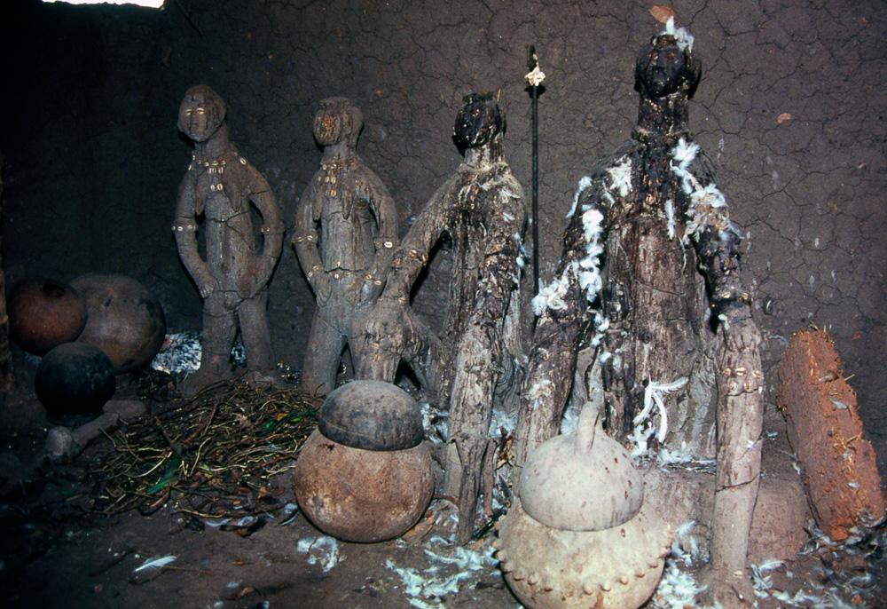 Intérieur d'une maisonnette-autel d'un devin-guérisseur, avec ses couples de génies modelés en terre. Village de Tógó. Photo Daniela Bognolo,1985.