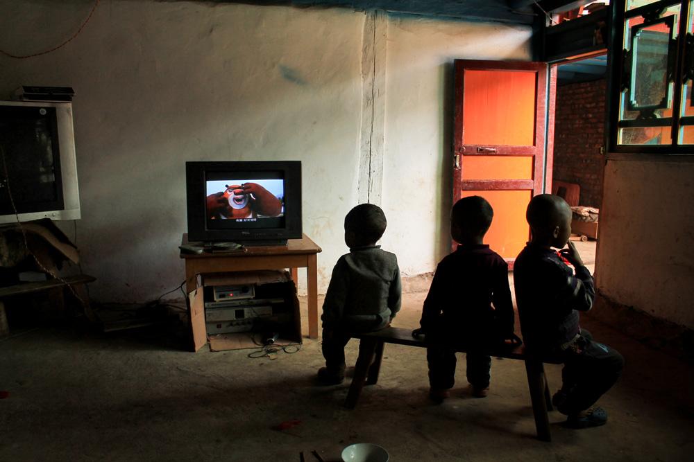 Séance télé pour de jeunes na. Aujourd'hui, toutes les maisonnées possèdent une télévision. Celle-ci fonctionne lorsque la production de courant dans la rivière est assez puissante. Photo Pascale-Marie Milan, 2013.