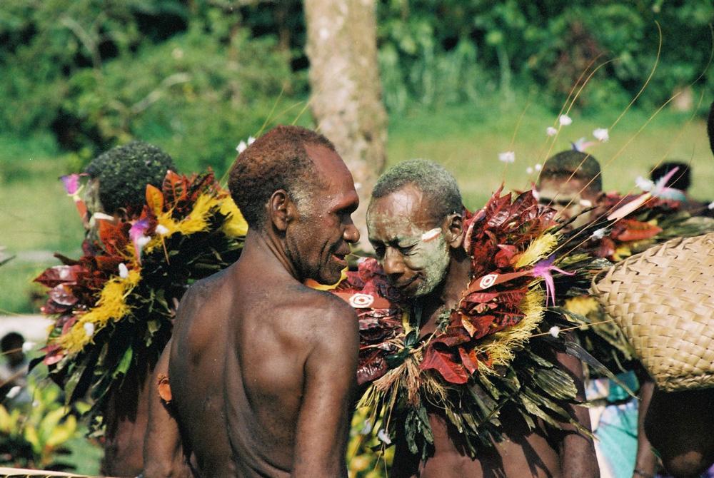 """Patrik Kameta, """"ainpindik"""" de la loge """"tombuan"""" de Satulai, accueillant Anton Tengmil, propriétaire d'un """"tombuan"""" de Pikan (un village voisin) qui a organisé une danse """"limbung"""" avant le spectacle de masques """"tombuan"""" de Satulai. Noter le motif d'œil """"tombuan"""" peint sur deux feuilles de la collerette de Tengmil. Verambif, village de Natong. Photo Antje S. Denner, 2001."""