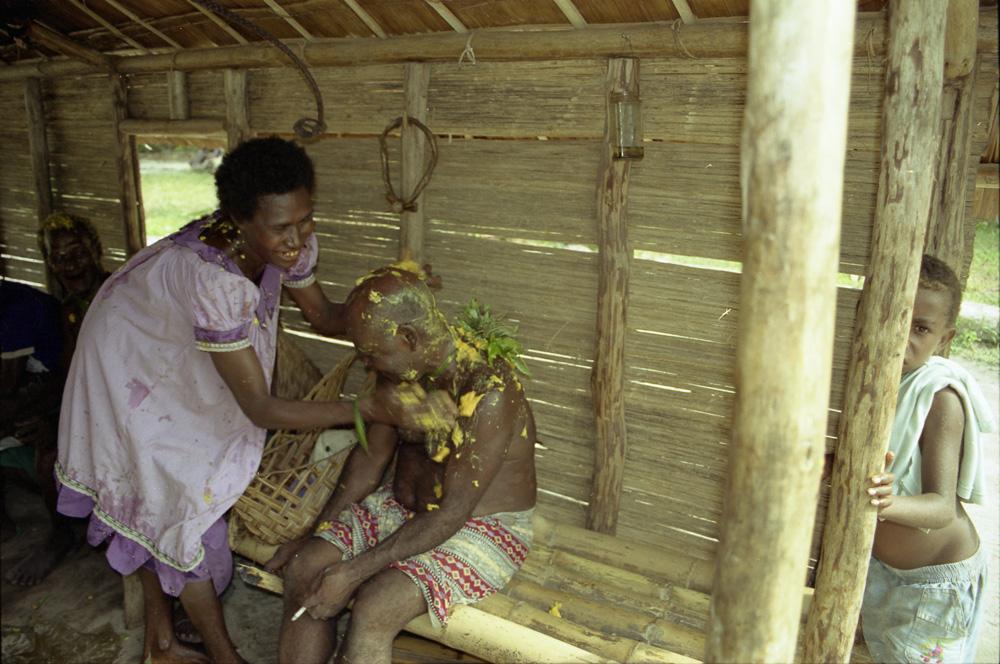 """Pièce rituelle """"telfangfang"""" : Christine Tinkiol """"savonne"""" Francis Neantele, un chef âgé, avec de la pulpe de bananes mûres. Balantembi, village de Banakin. Photo Antje S. Denner, 2001."""