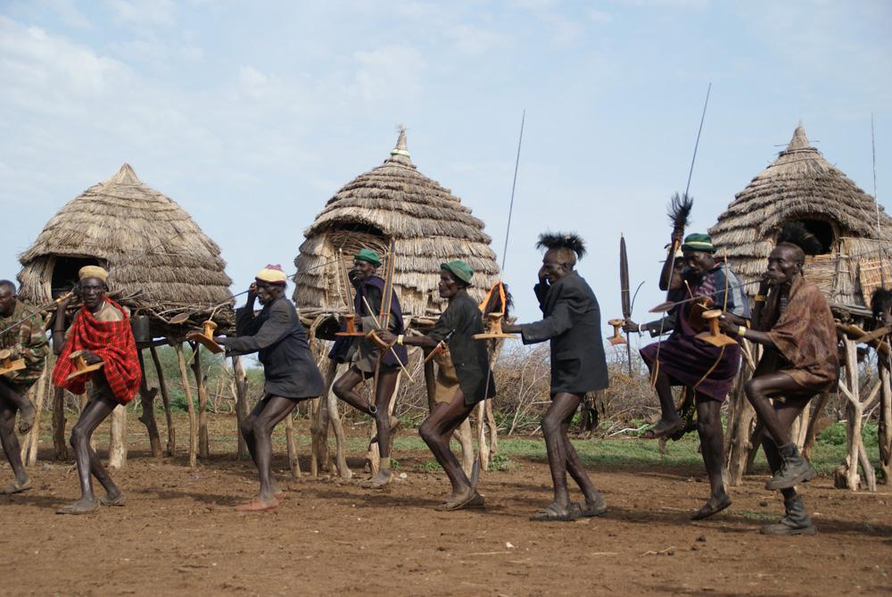 Les hommes de la génération des Ngikaleeso effectuent une danse nyakidamadam musclée en l'honneur des derniers survivants de la génération aînée des Nguwana (Toposa-NgiPeymong). Photo Gustaaf Verswijver.