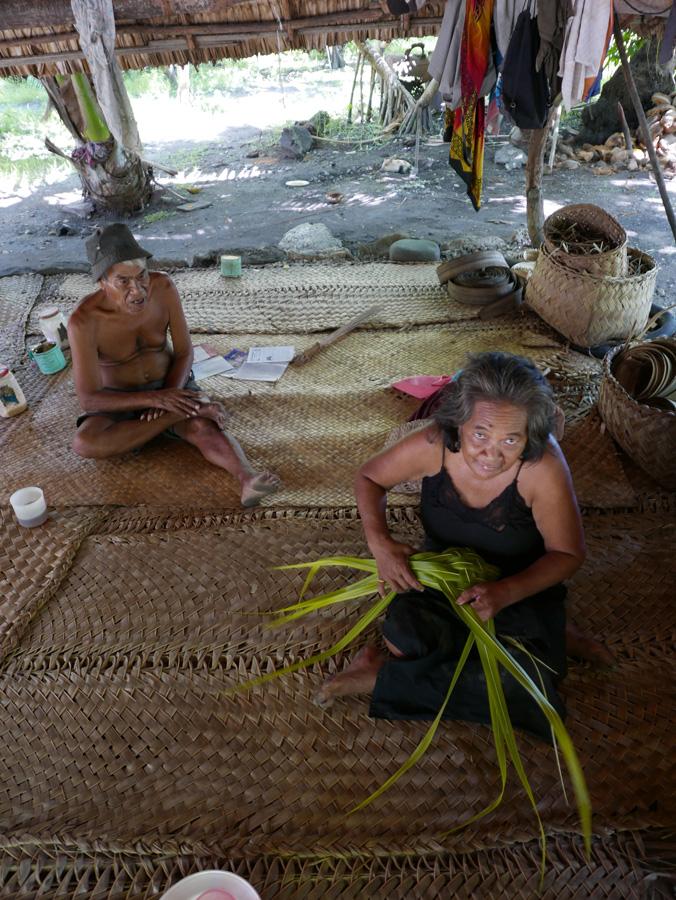 Taburimai et son épouse, confectionnant un panier de feuille de cocotier destiné à trans- porter un pudding de fruit de pandanus. Tanaeang, Tabiteuea nord. Photo Guigone Camus, 2015.